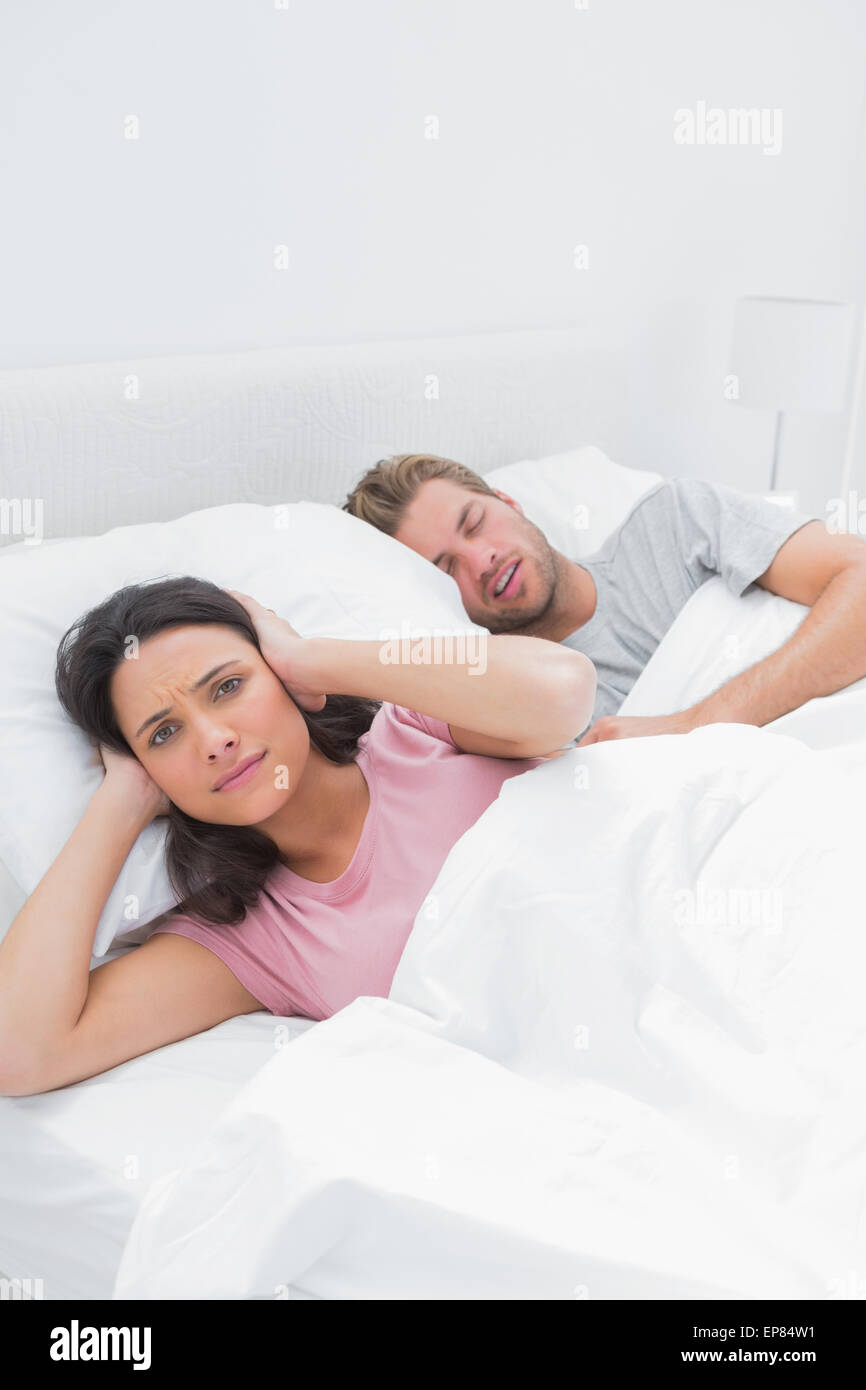 Annoyed woman covering her ears while her husband is snoring - Stock Image
