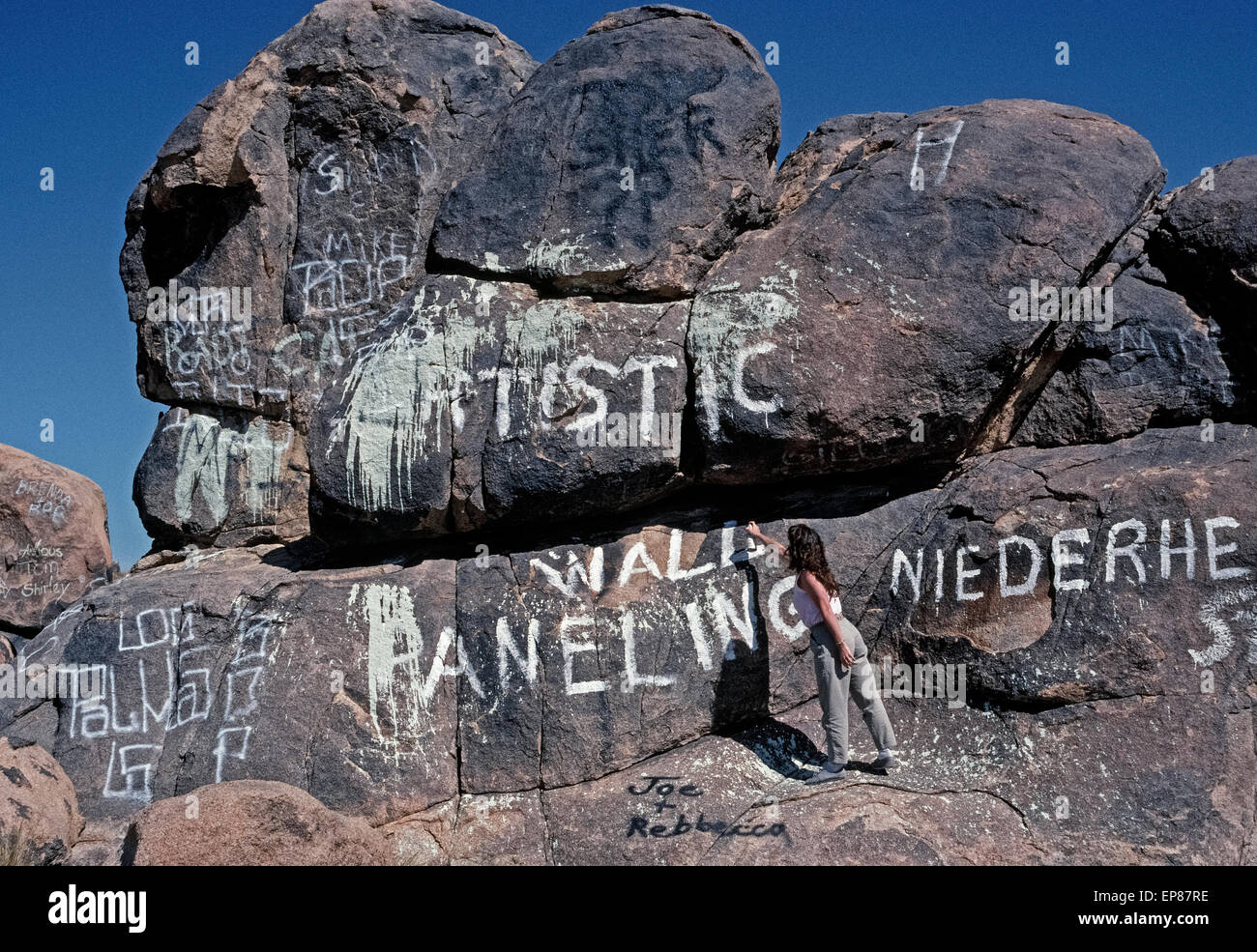 Spray-painted names and other graffiti deface the boulders and natural scenery in the desolate Mojave Desert near Johnson Valley in San Bernardino County in Southern California, USA. Cans of white, black or colored aerosol paints are commonly used to disfigure the rocks without any artistic effort often seen with   graffiti in urban areas. Stock Photo