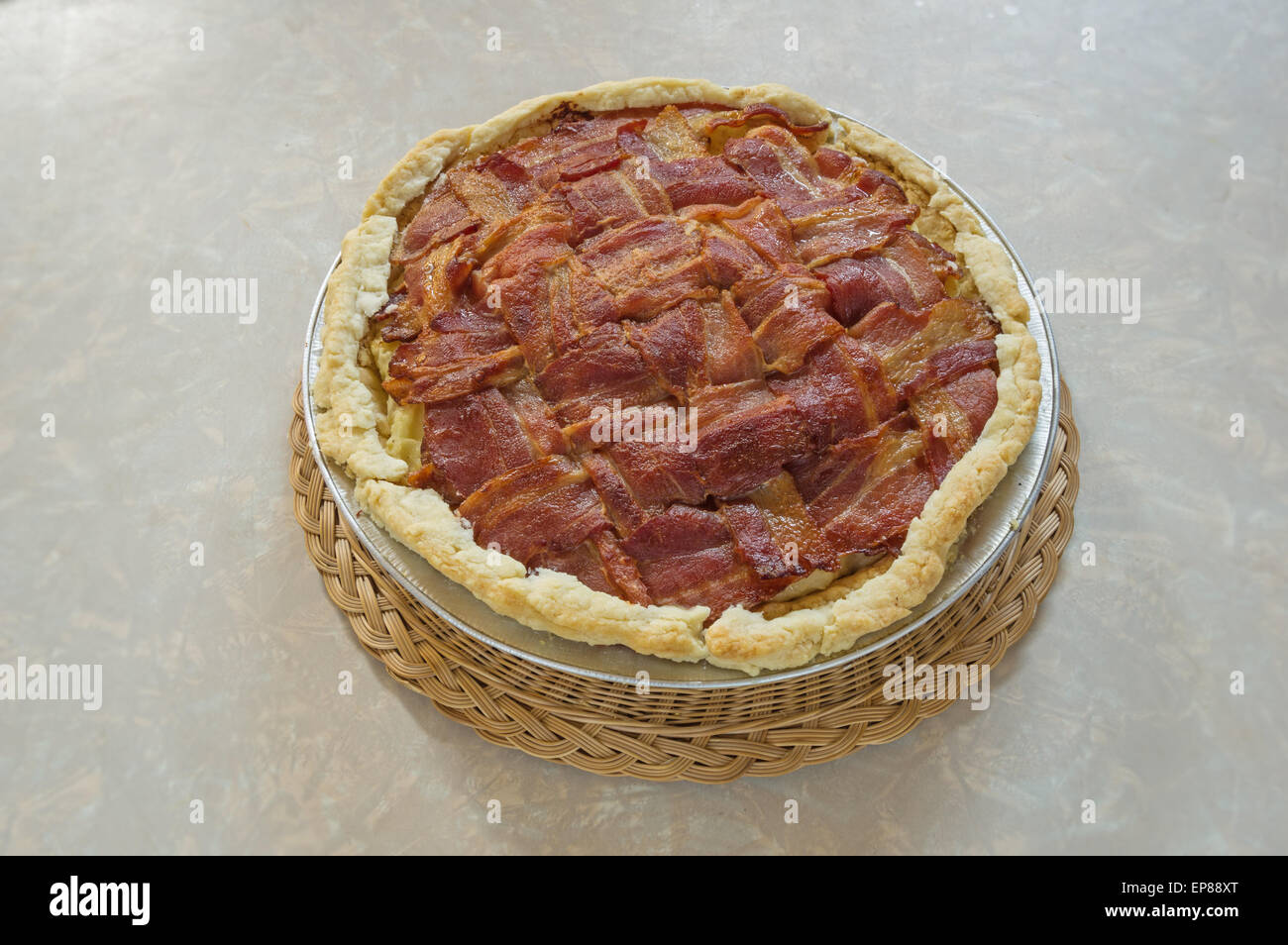 home made bacon lattice top mashed potato pie sitting on table on a wicker hot pad - Stock Image