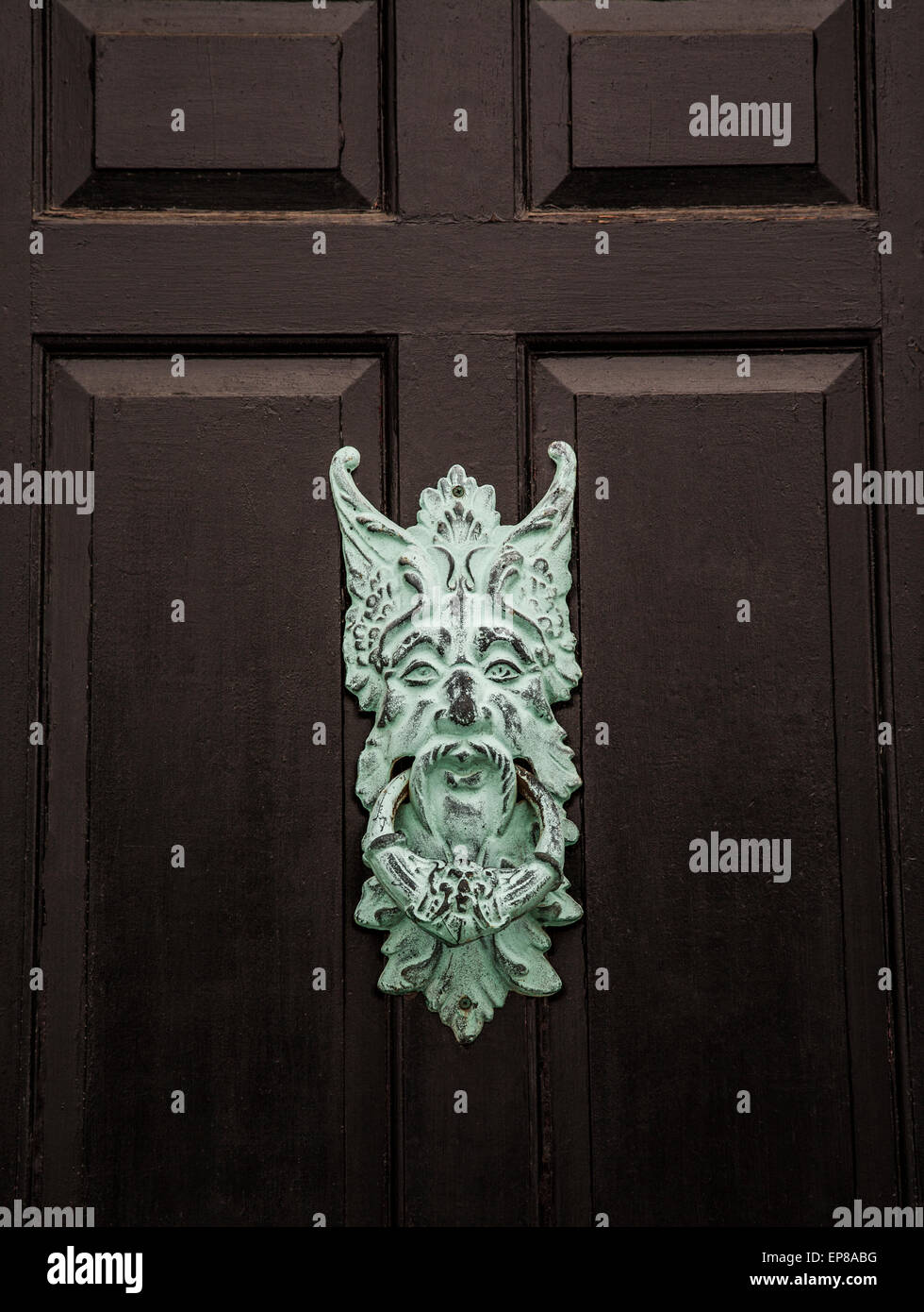 Black wooden front door entrance with a close up Gothic door knocker face and handle, USA, US, spooky door mysterious - Stock Image