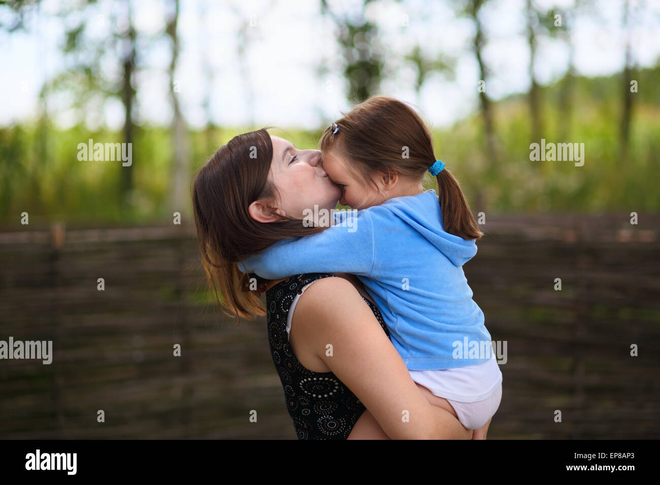 A mother's love. Mom keeps little daughter in her arms and kisses her on the forehead. Selective on the faces - Stock Image