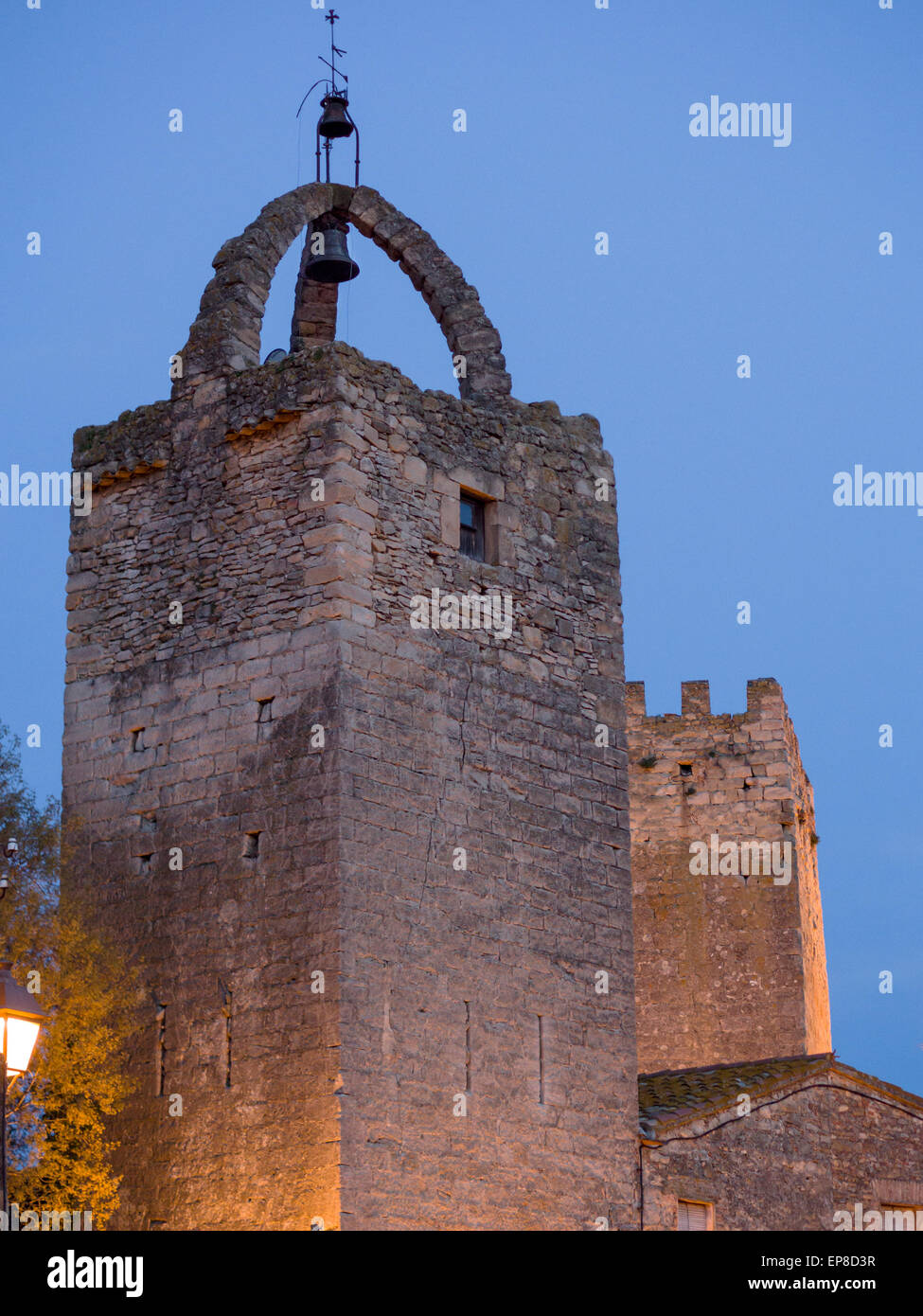 Ancient Belltower at Peratallada at Dusk. The large bell is hung from a triple arch at the top of a massive square - Stock Image