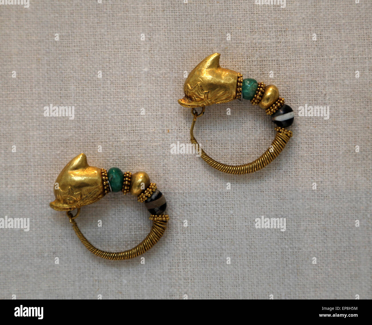 Pair of gold earring with dolphin's heads with emerald, glass and gold beads. Greek. 2nd-1st century B.C. - Stock Image