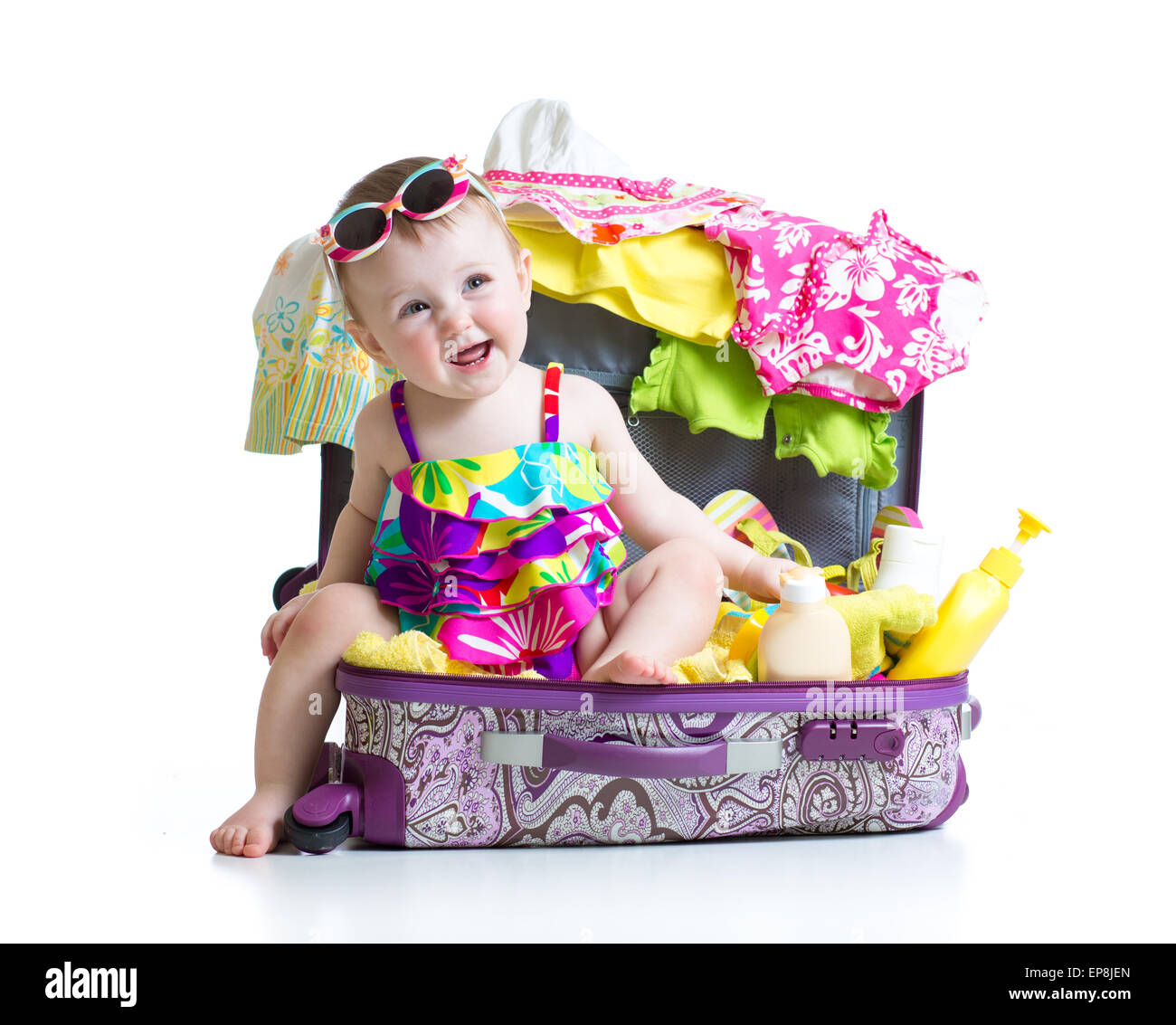 Child girl sitting in suitcase with things for vacation travel - Stock Image