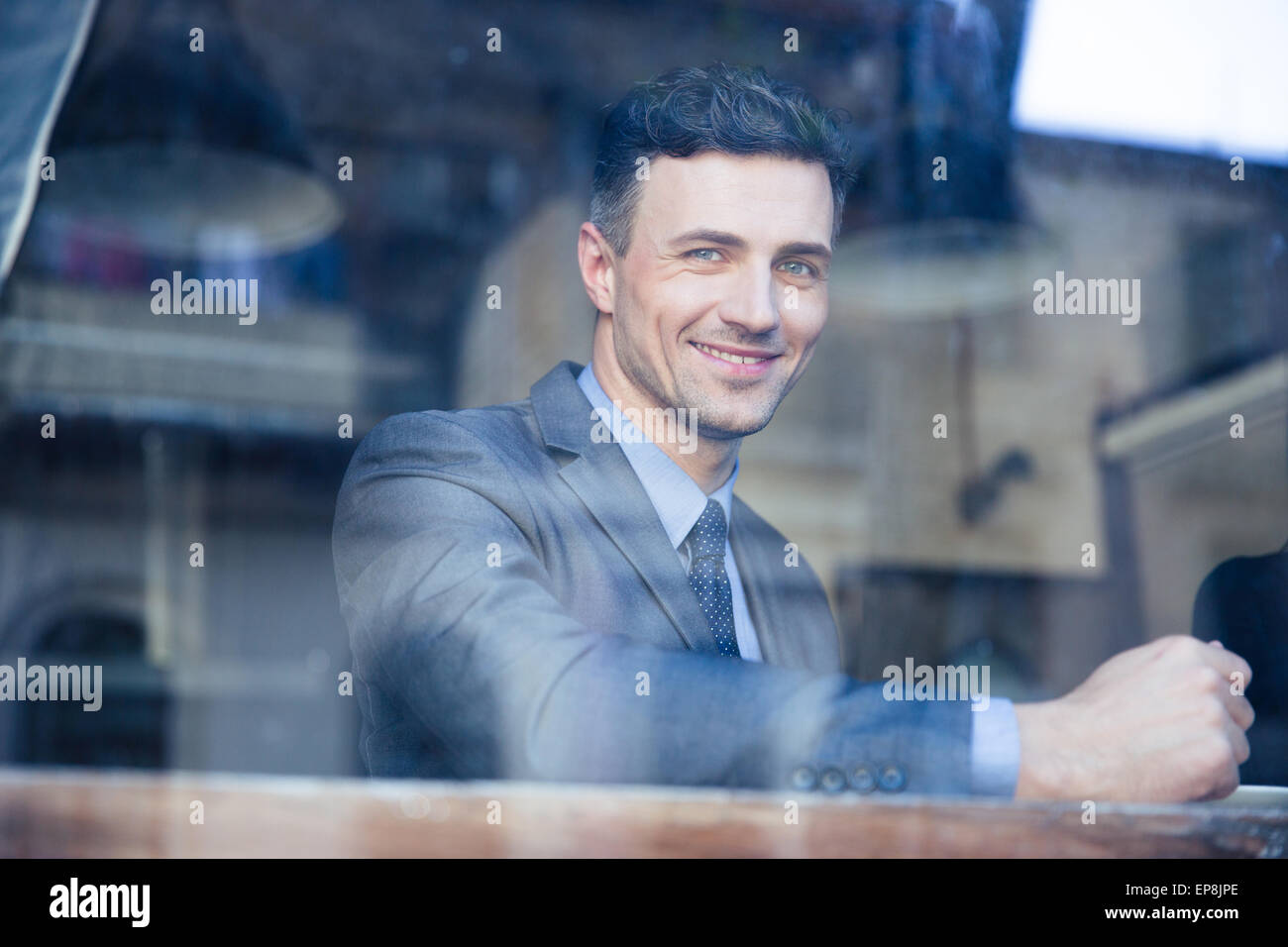 Portrait of a cheerful businessman sitting at the table in cafe - Stock Image