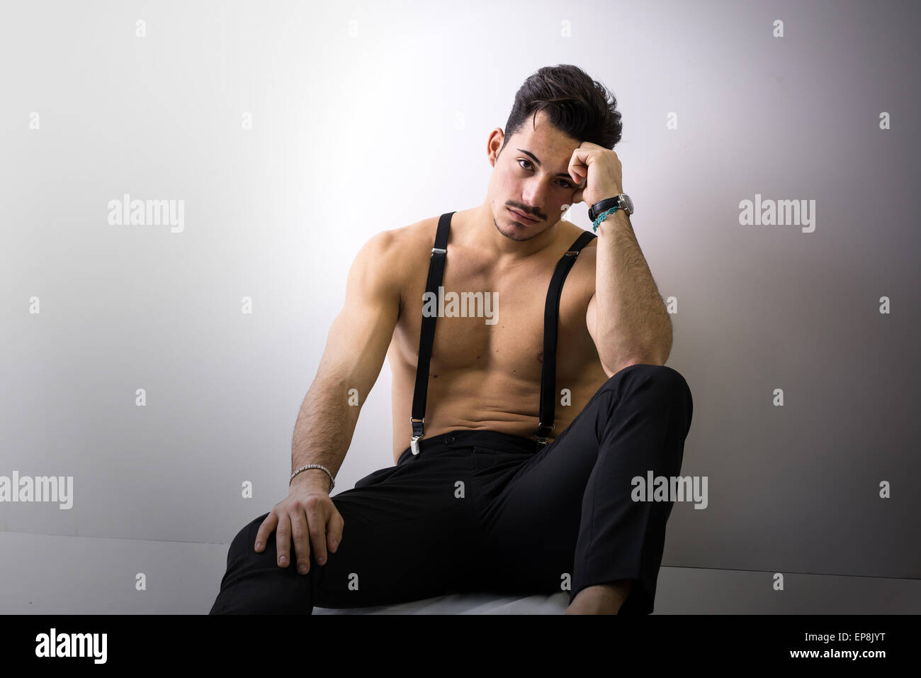 Shirtless athletic young man with suspenders and black pants sitting on floor, looking at camera - Stock Image