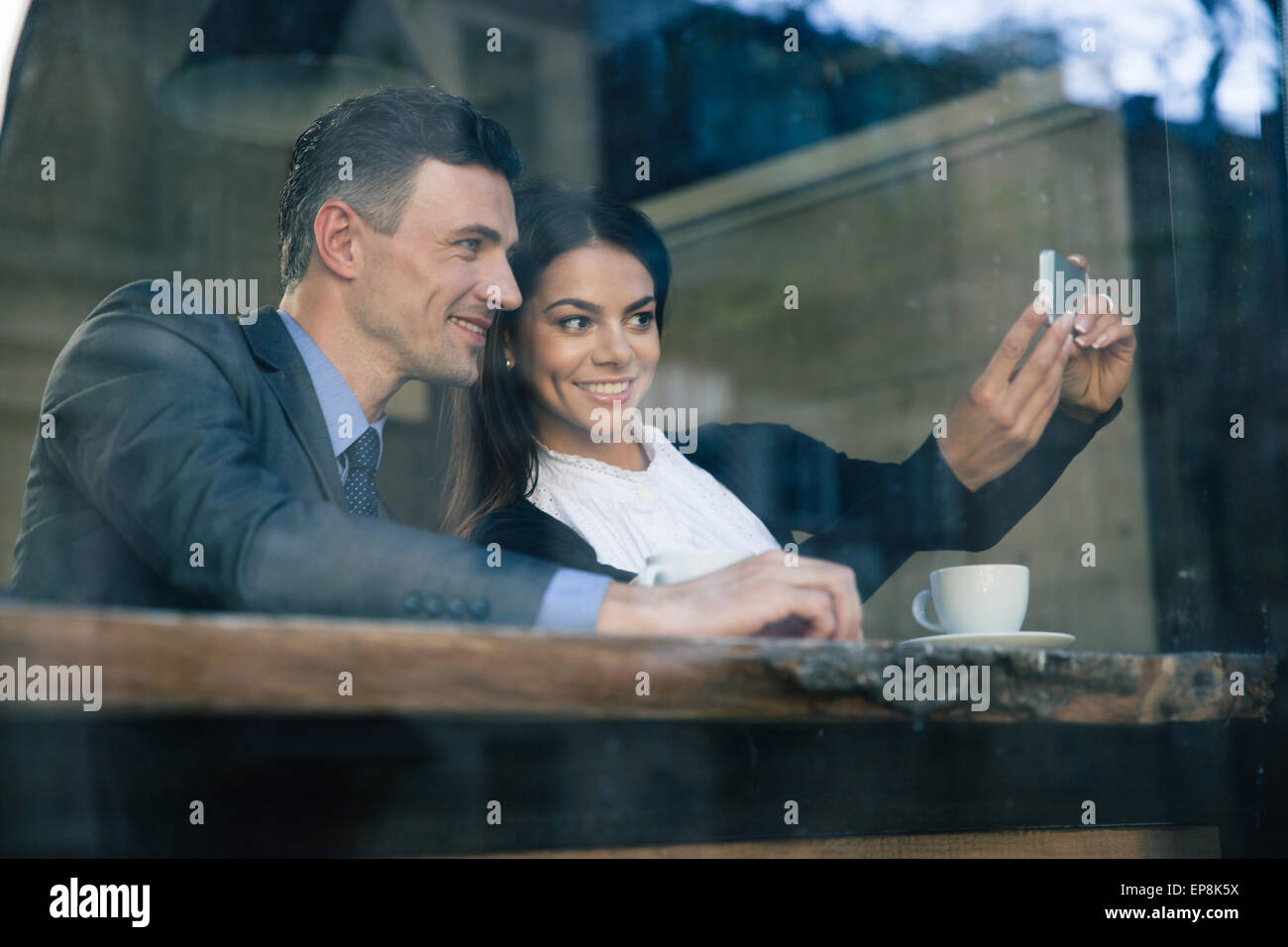 Smiling businesswoman and businessman making selfie photo on smartphone in cafe - Stock Image