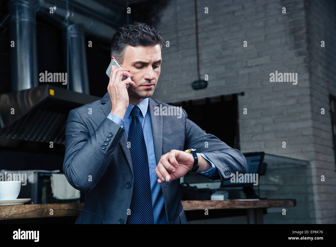 Confident businessman speaking on the phone and looking on the wristwatch in cafe Stock Photo