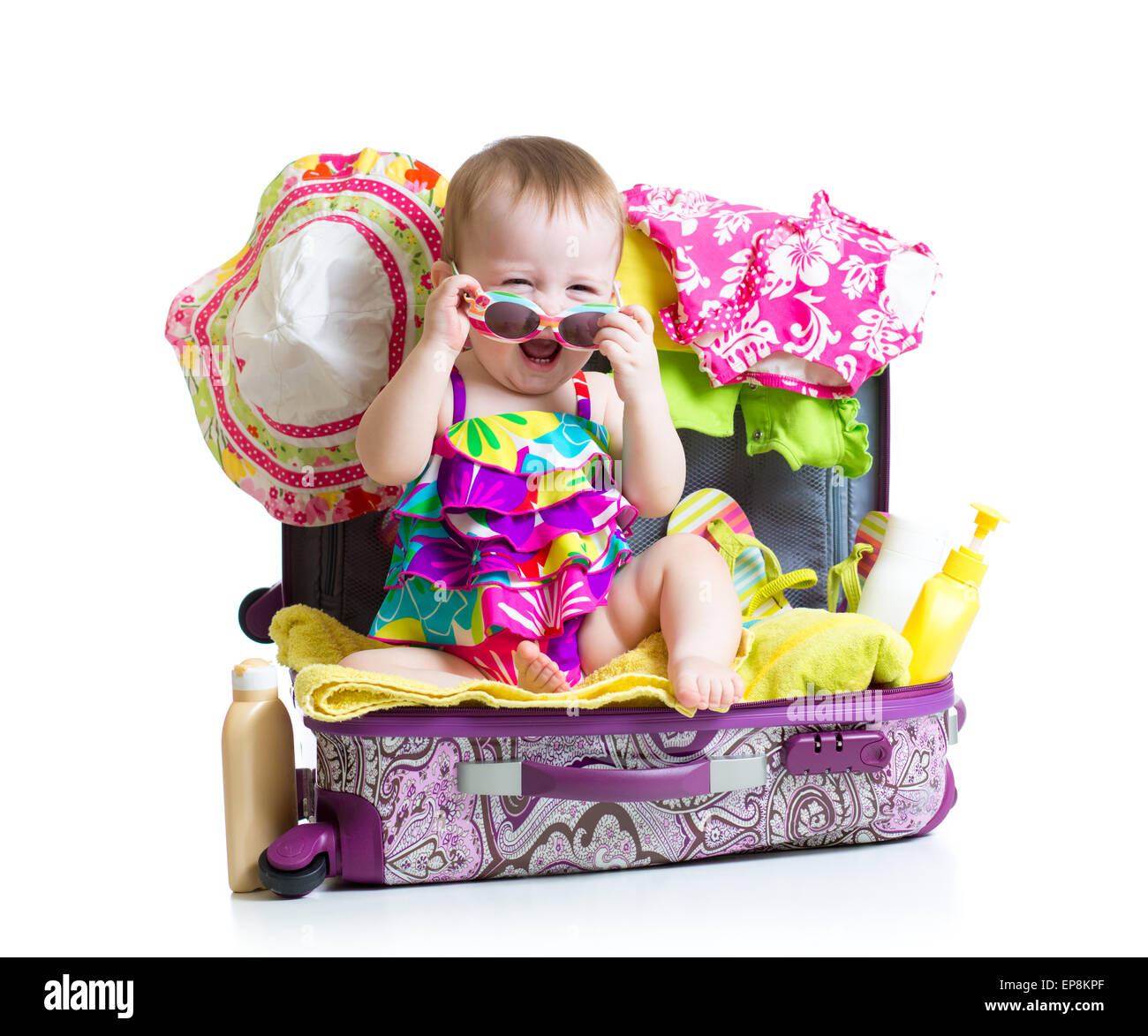 Baby girl sitting in suitcase with things for vacation travel - Stock Image