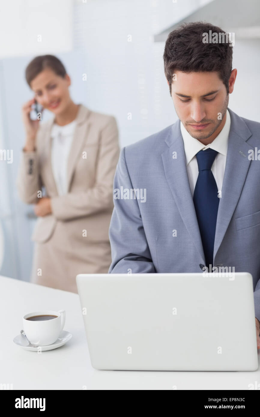 Businessman using a laptop before going to work - Stock Image