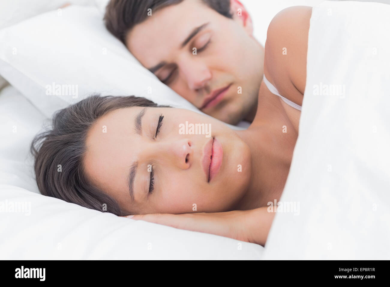 Portrait of an attractive woman sleeping next to her partner - Stock Image