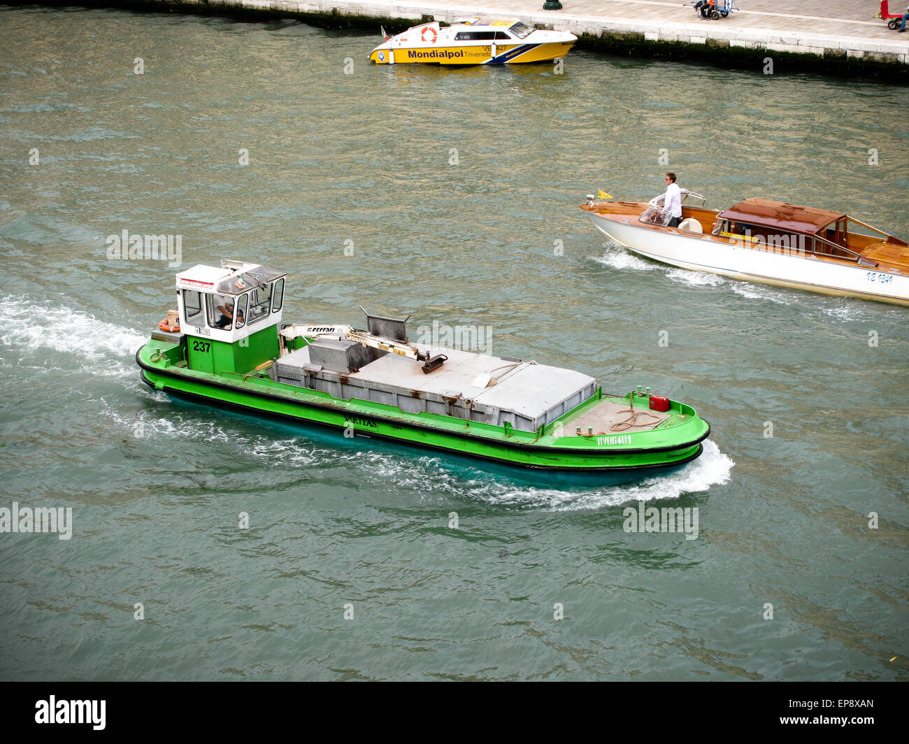 A green commercial boat on the Grand Canal in Venice - Stock Image