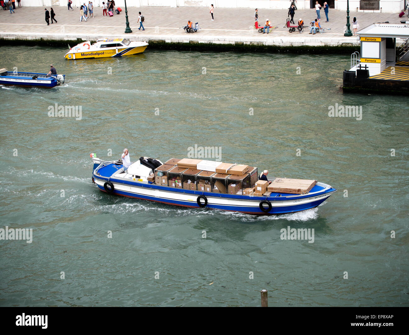 A blue commercial boat loaded with goods on the Grand Canal in Venice - Stock Image