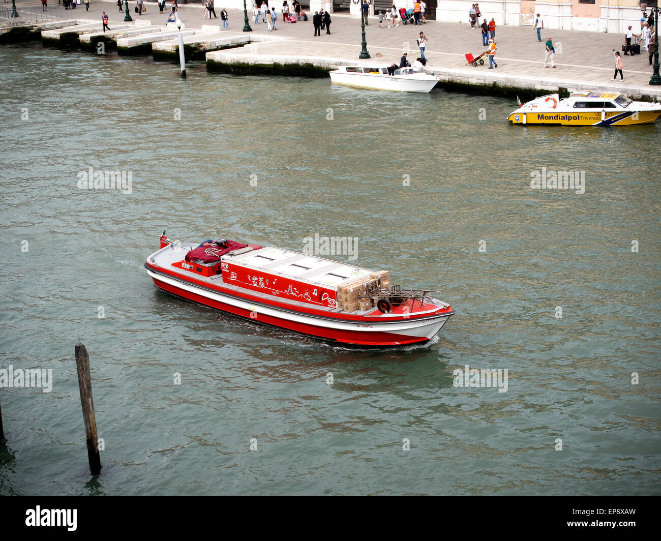 A red commercial boat on the Grand Canal in Venice - Stock Image