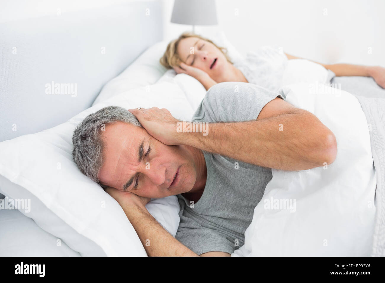Tired man blocking his ears from noise of wife snoring - Stock Image