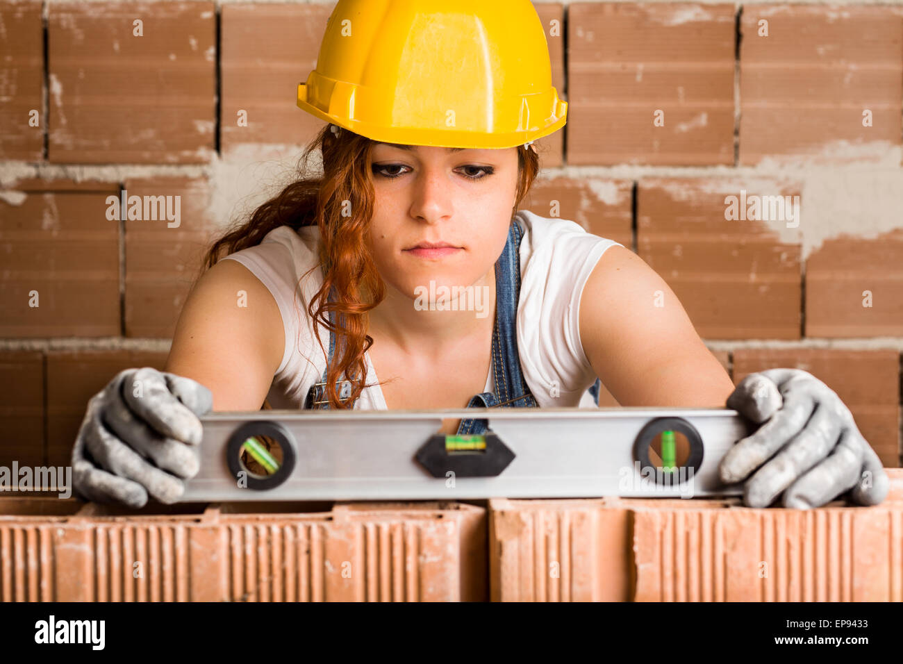 Woman Bricklayer with Helmet Holding a Spirit Level on a Brick Wall - Stock Image