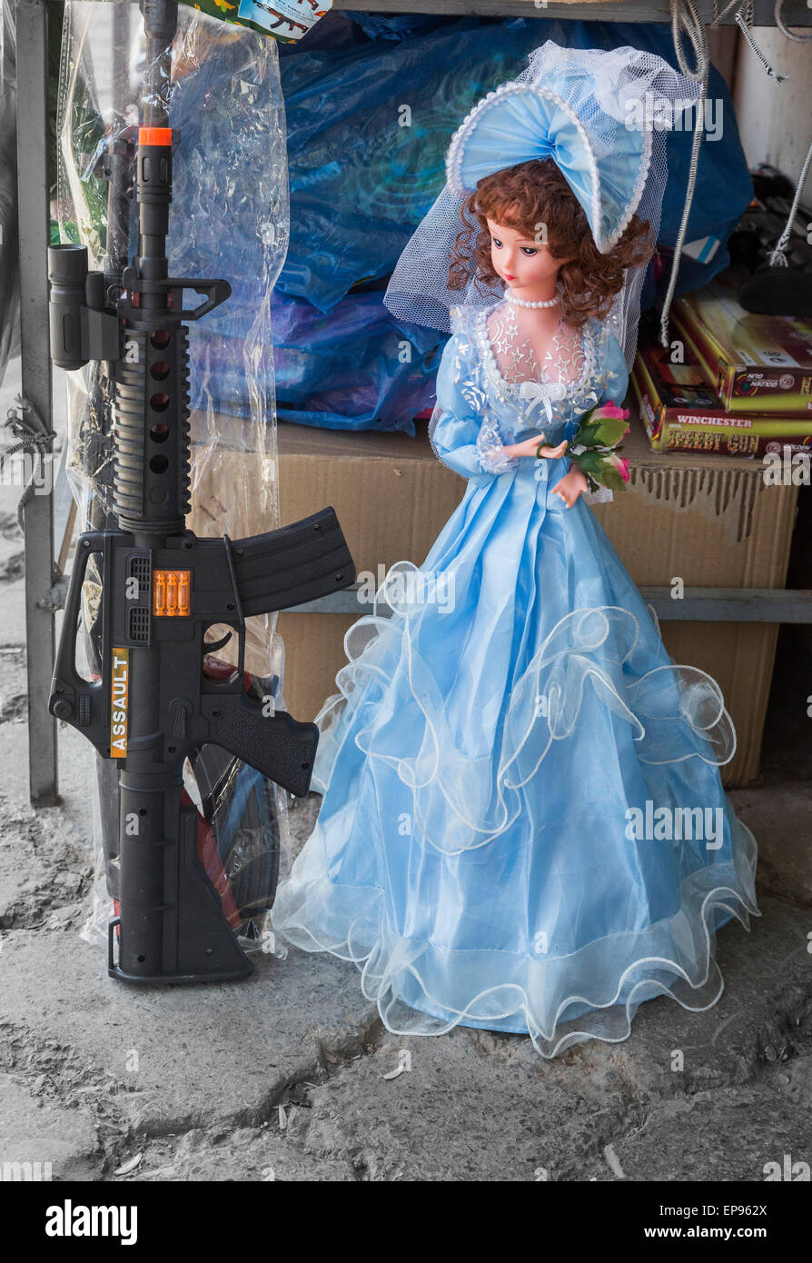 Princess bride doll and machine gun toys side by side, bazar, Zahedan, Iran - Stock Image