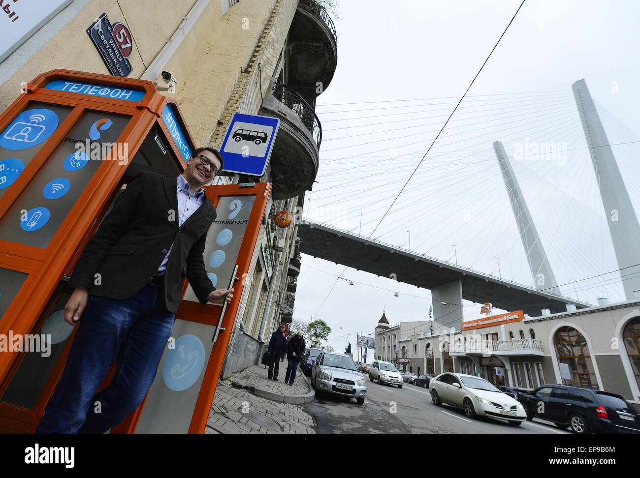 Vladivostok, Russia. 15th May, 2015. A local resident walks out of a multifunctional telephone booth that has been - Stock Image