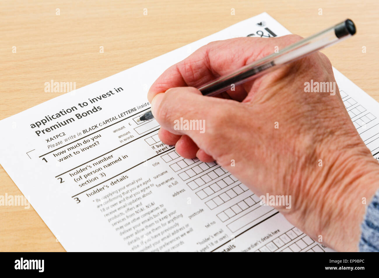 Wealthy elderly senior pensioner completing an application form to buy investments in Premium Bonds. England UK - Stock Image