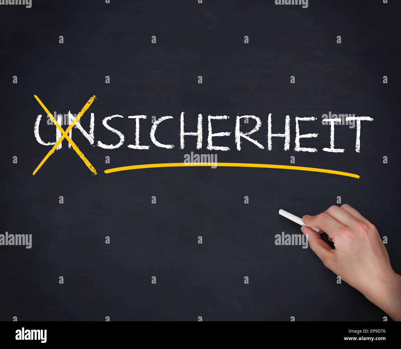 Hand crossing out the german word unsicherheit - Stock Image