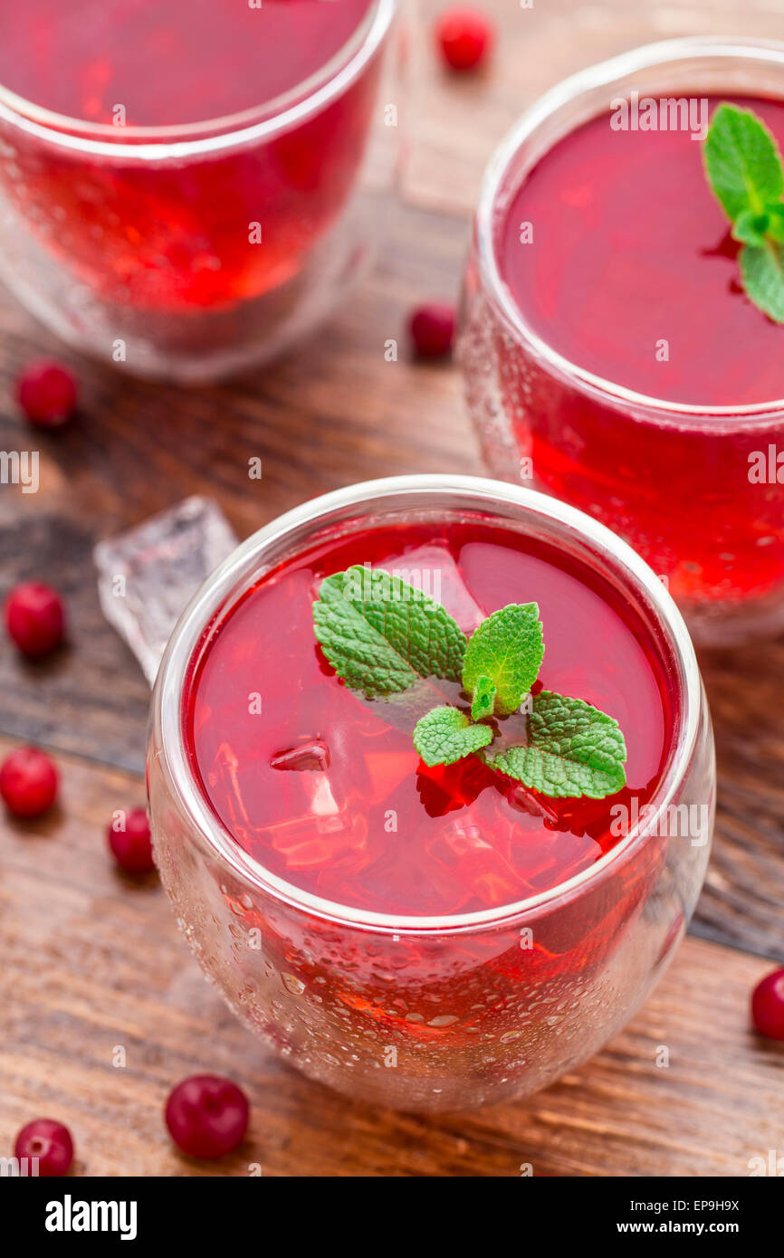 Cranberry cocktail with mint garnish on a wooden table - Stock Image