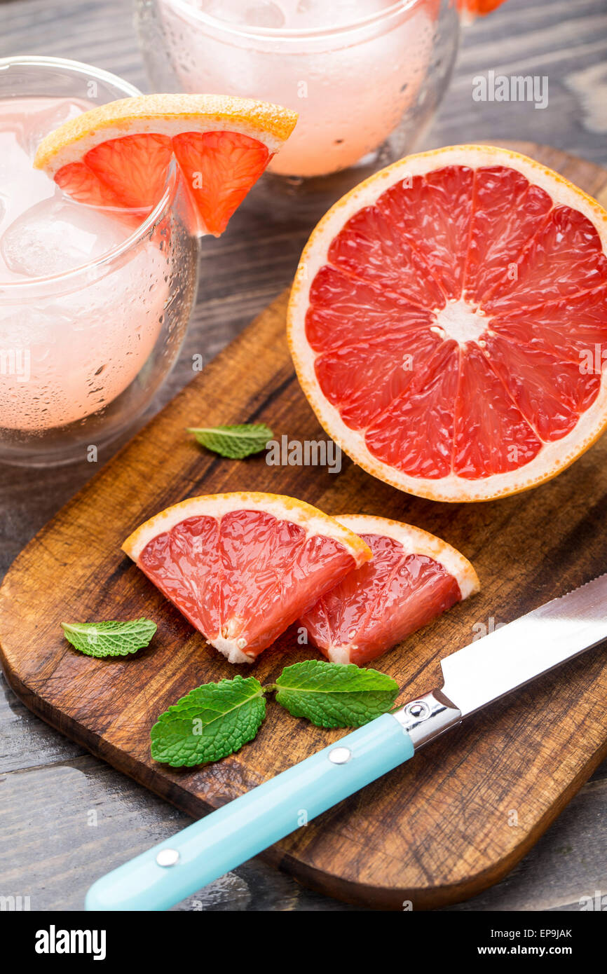 Grapefruit with slices on a wooden table. - Stock Image