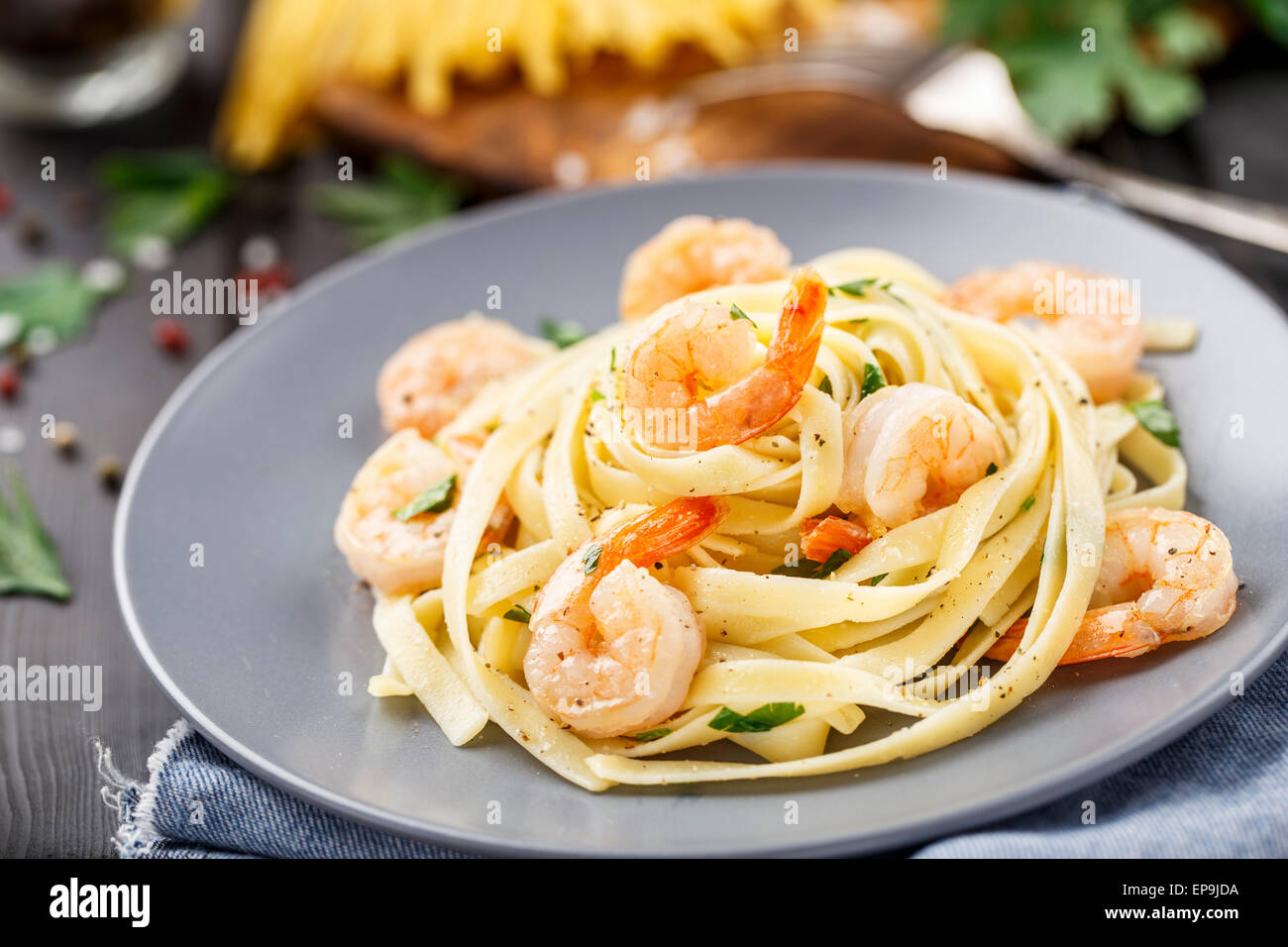 Tagliatelle with shrimps and parsley on a plate - Stock Image