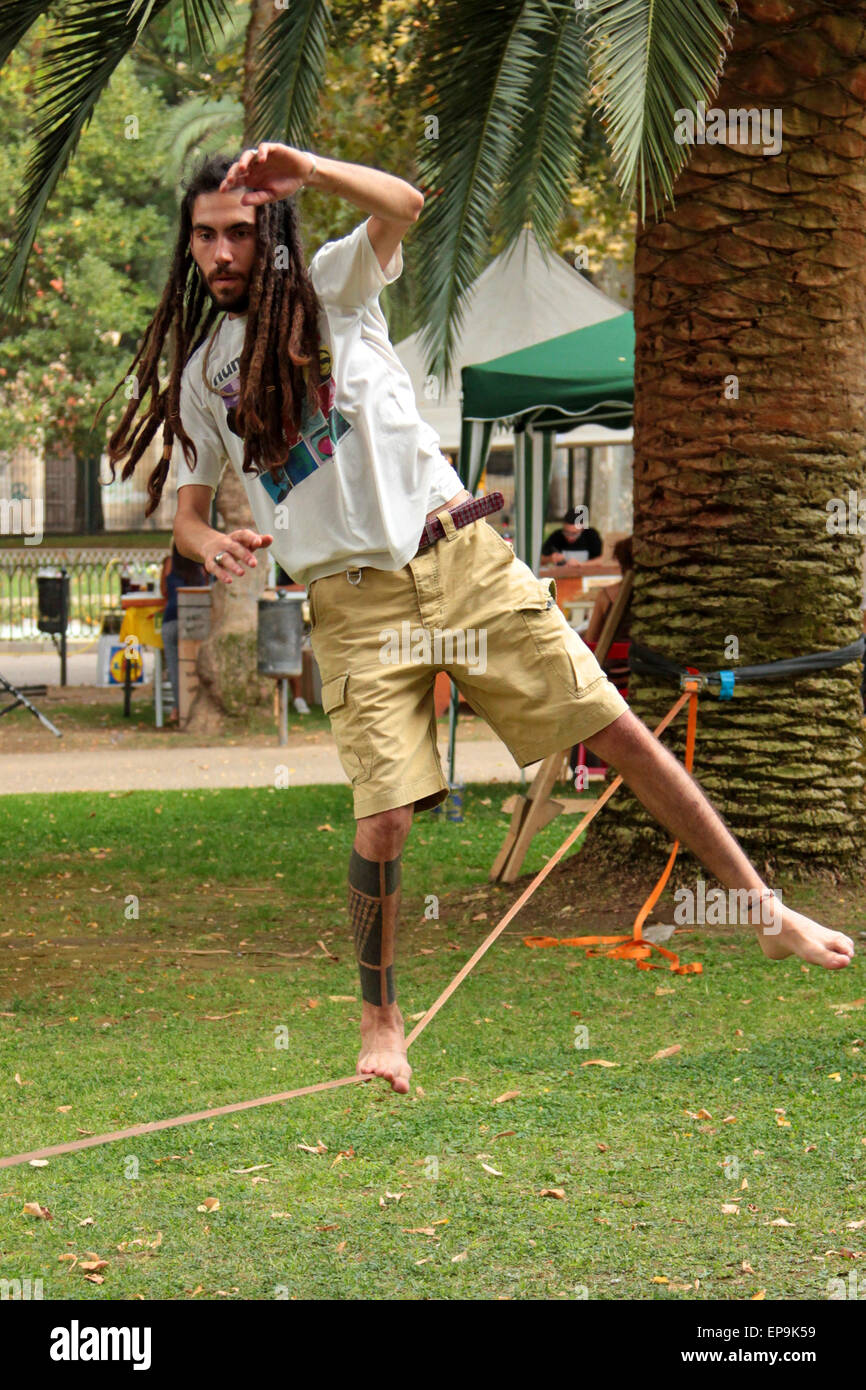 Man with dreadlocks and tattoos balancing on a tightrope - Stock Image