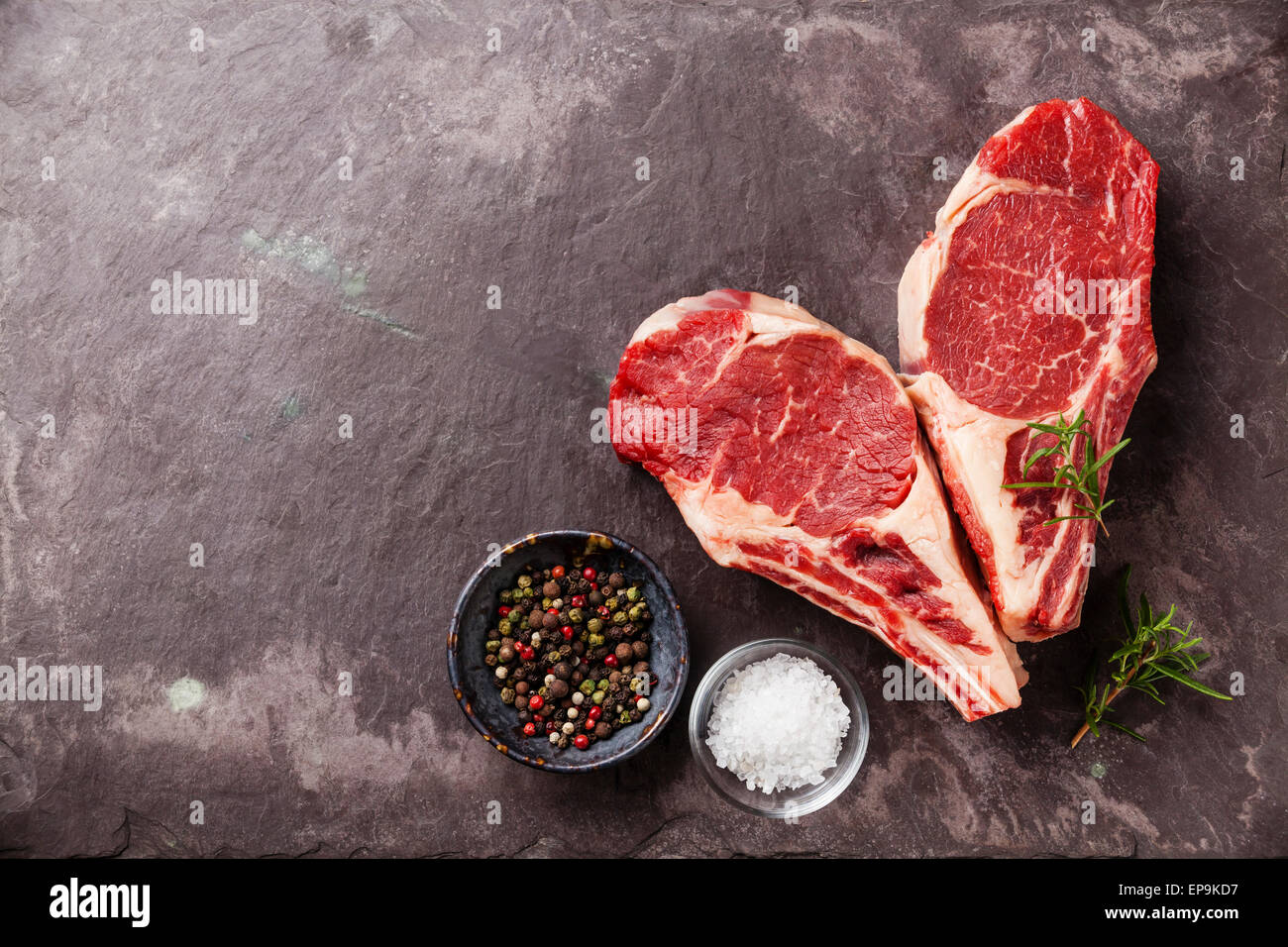 Heart shape Raw fresh meat Ribeye Steak with rosemary, pepper and salt on stone slate background - Stock Image