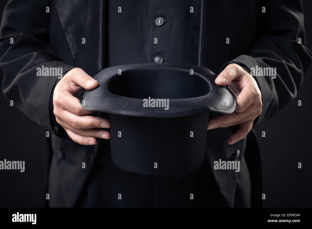 closeup of top hat in magician hands isolated - Stock Image