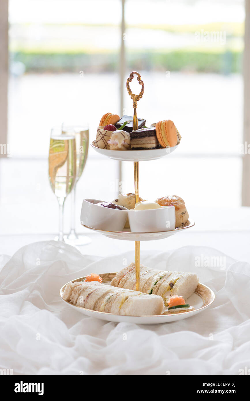 Afternoon tea with cakes, scones and finger sandwiches. - Stock Image
