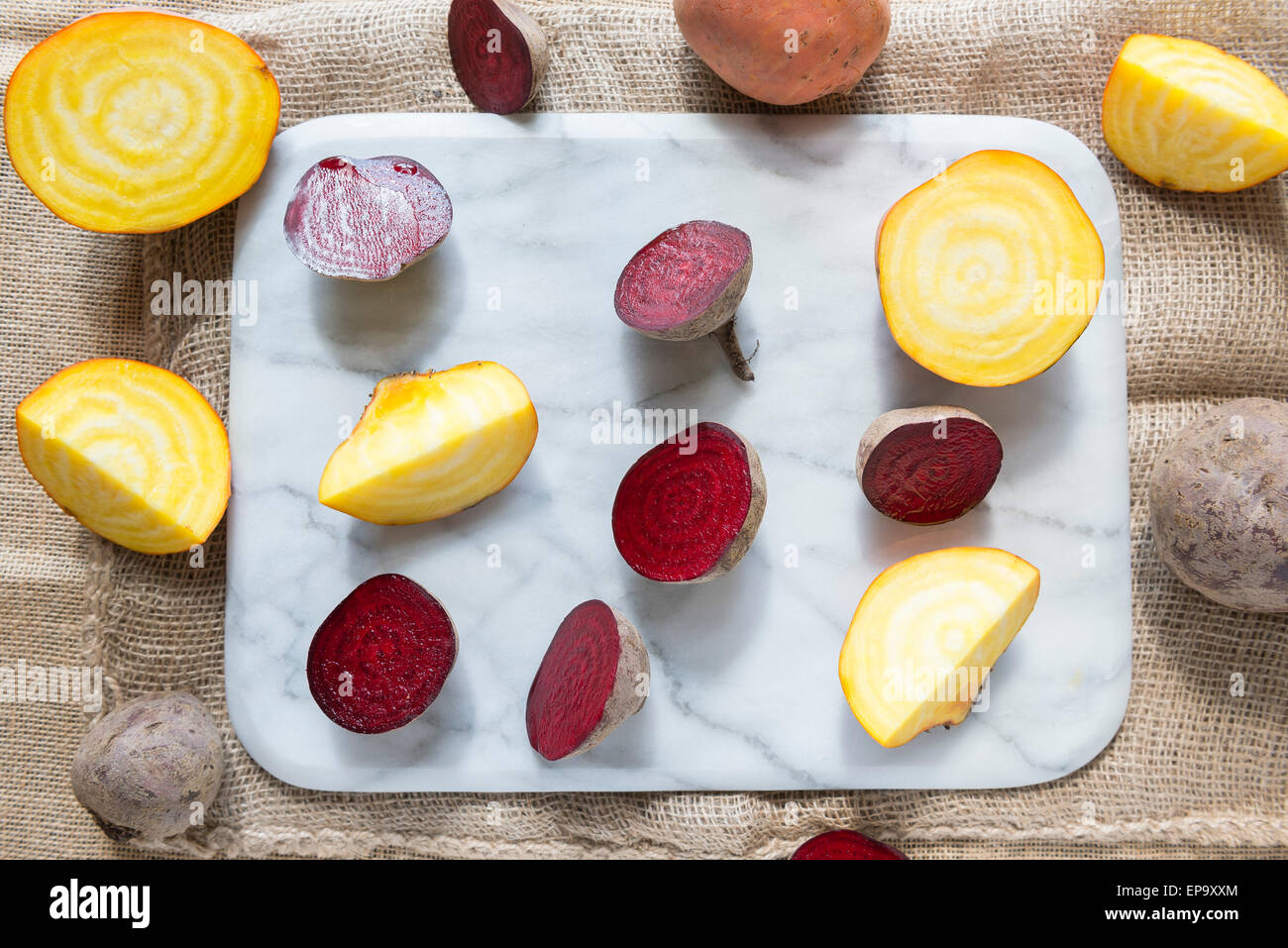 Red beetroot and golden beetroot on a marble chopping board. - Stock Image