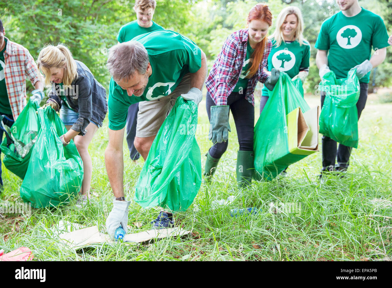 Woman Reaches To Pick Up Trash In The Park Royalty Stock Photo