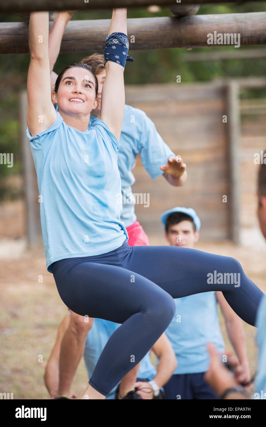 smiling woman crossing monkey bars boot camp - Stock Image