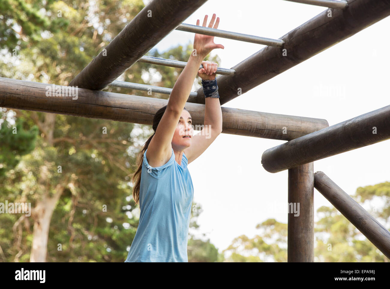 woman monkey bars boot camp obstacle course - Stock Image