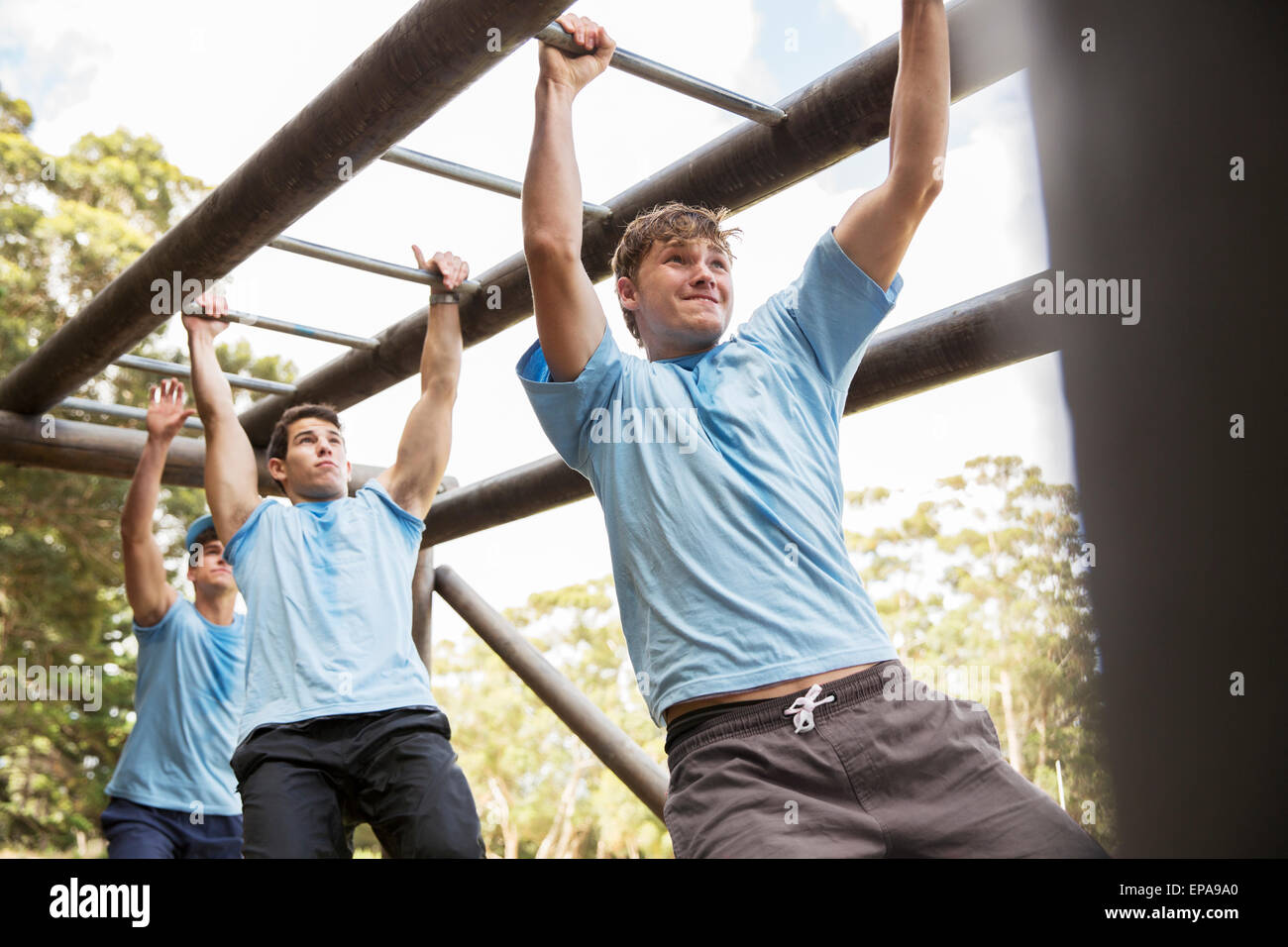 man monkey bars boot camp obstacle course - Stock Image