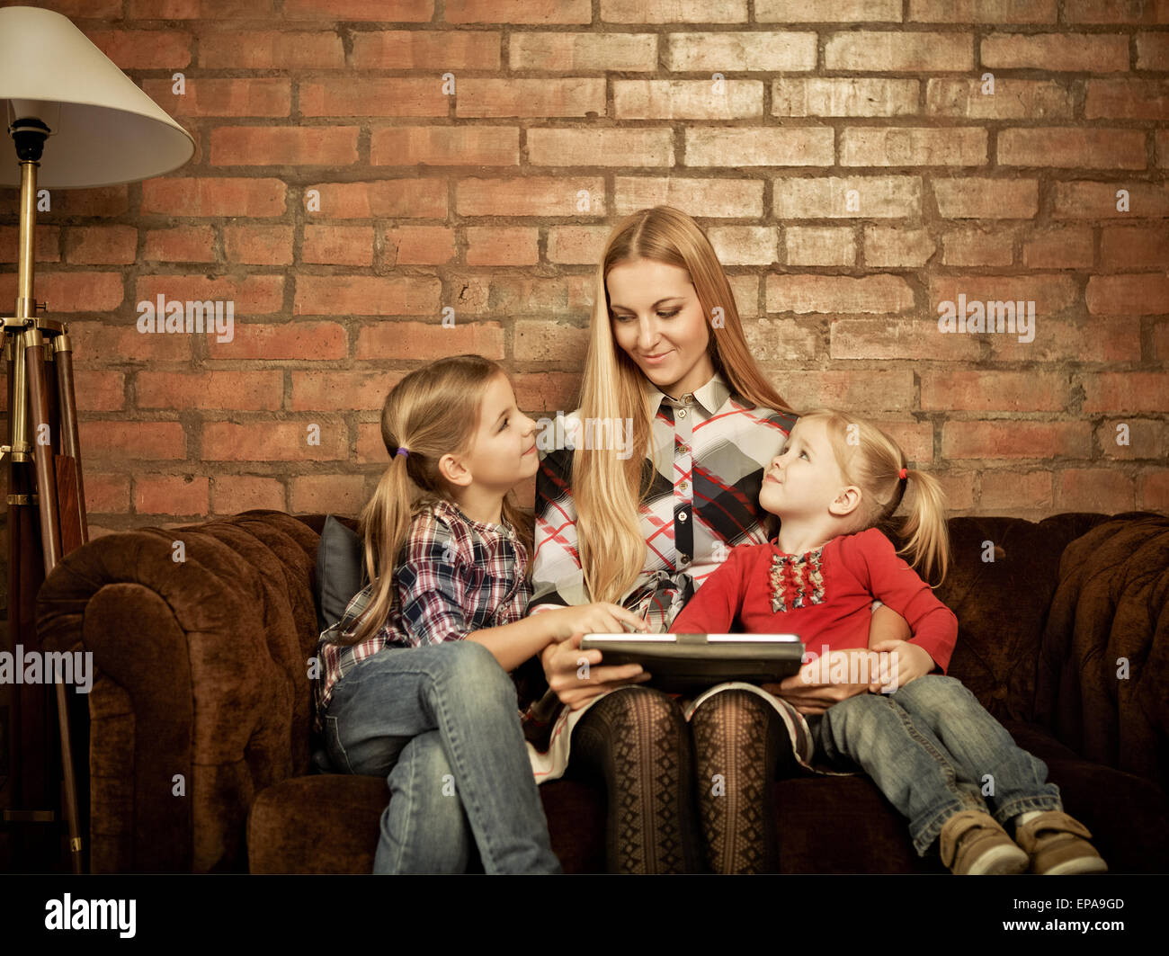 Happy mother and her little daughters indoors - Stock Image