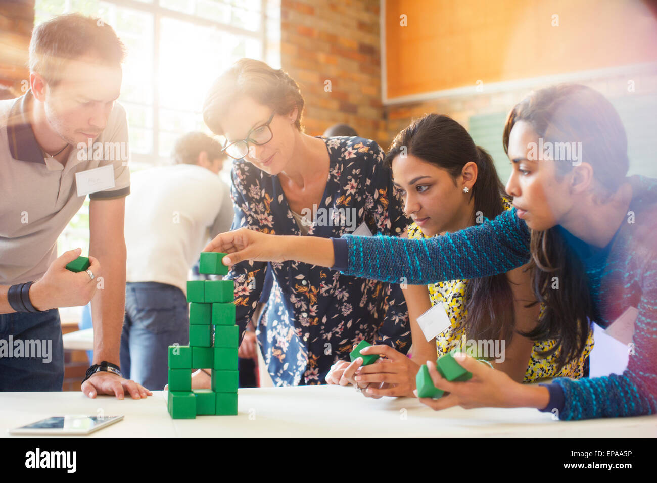 creative business people stacking green block - Stock Image