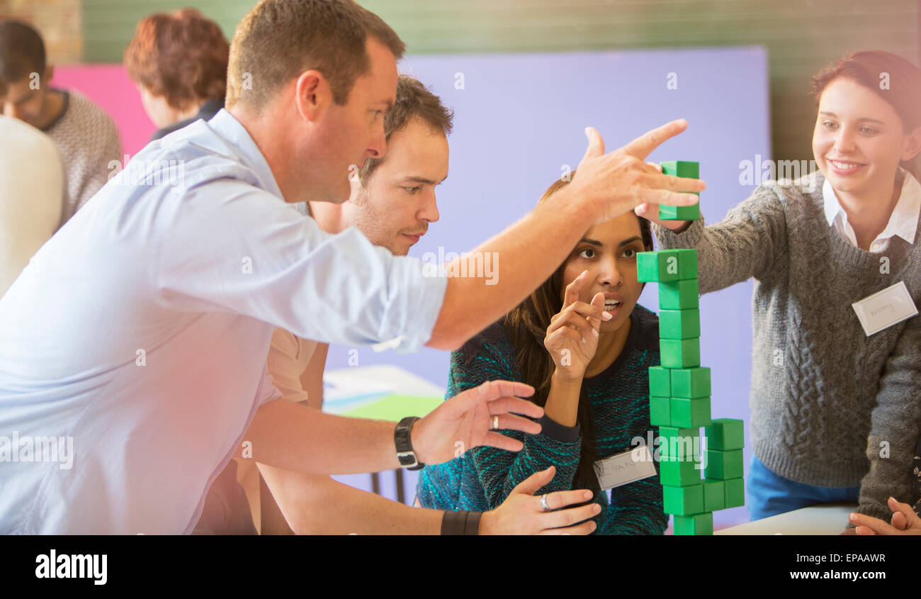business people stacking green block - Stock Image