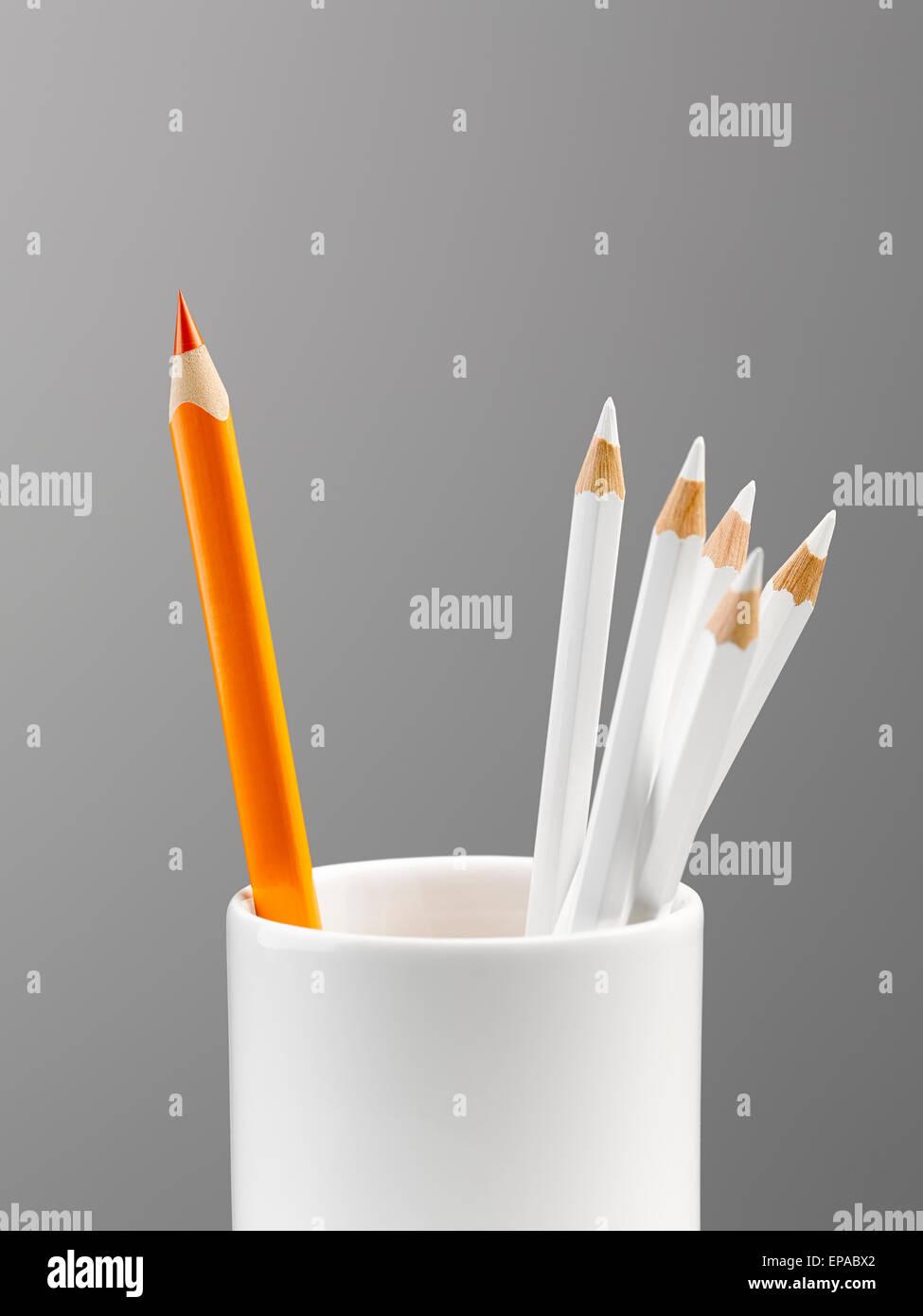 orange pencil cup white still life - Stock Image