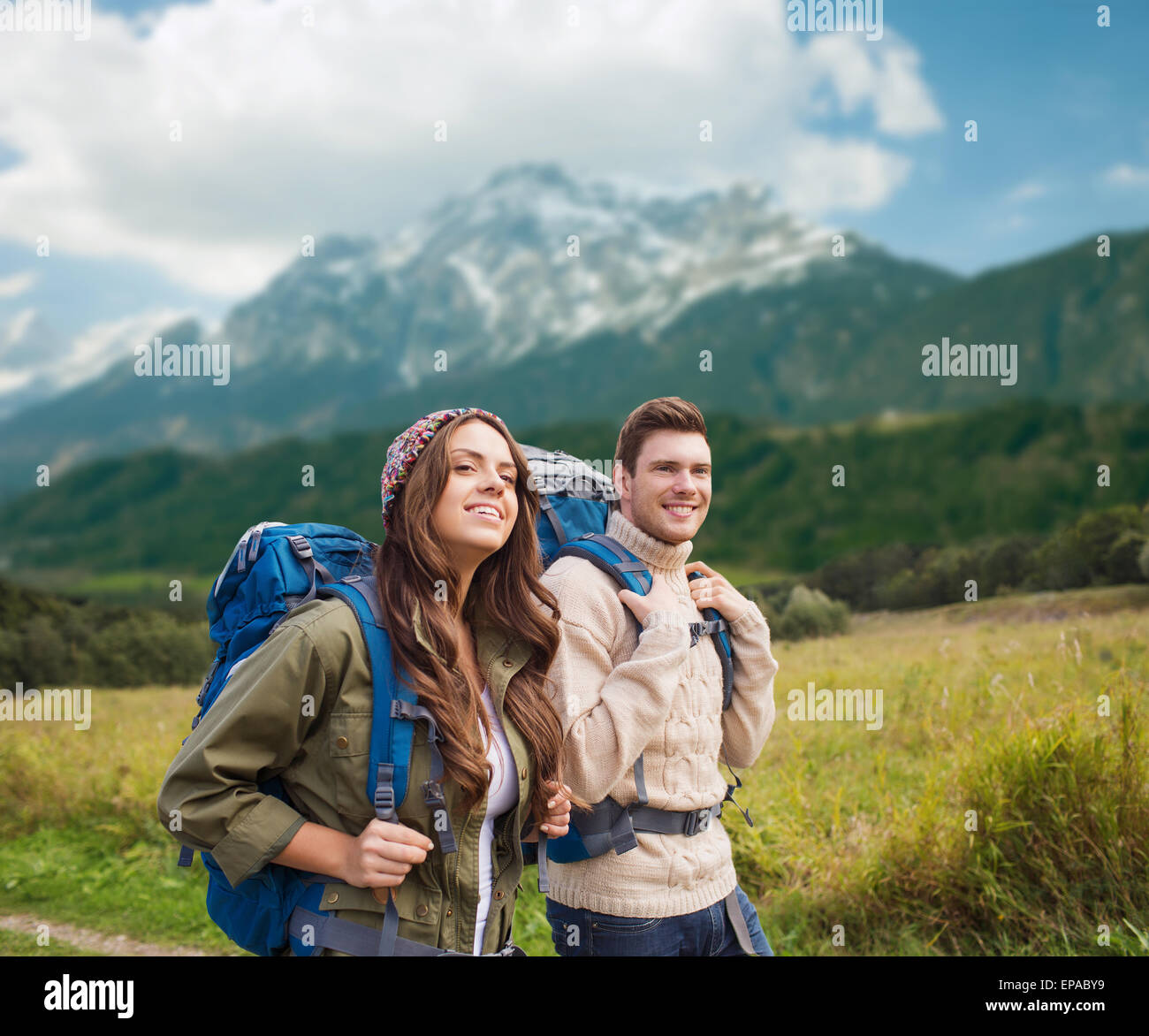 smiling couple with backpacks hiking - Stock Image