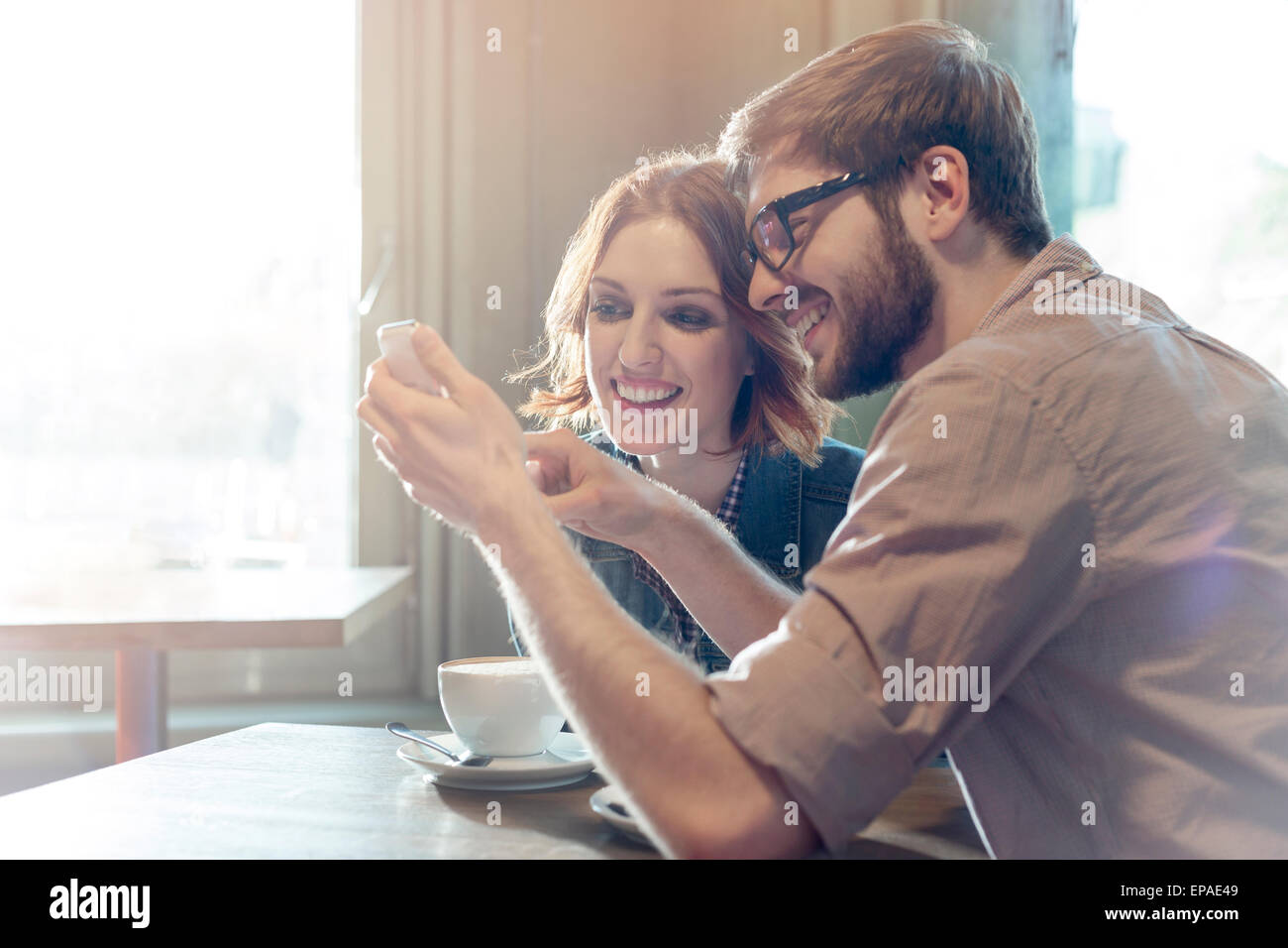 heterosexual couple using cell phone cafe - Stock Image