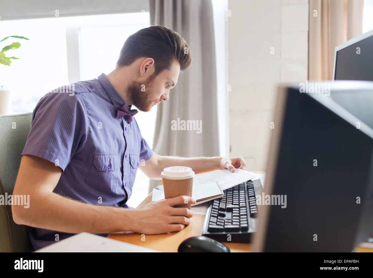 creative male worker drinking coffee and reading - Stock Image