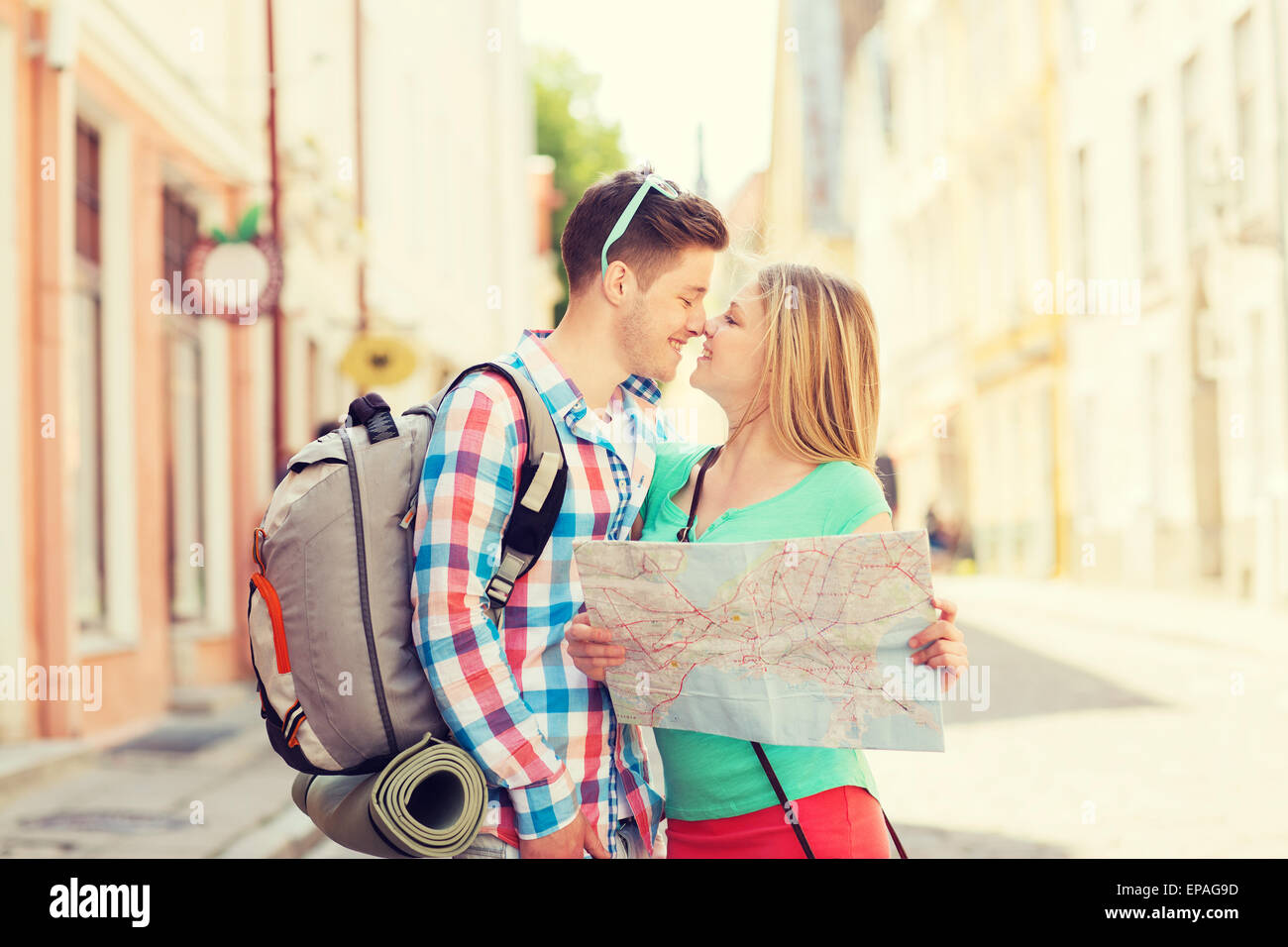 smiling couple with map and backpack in city - Stock Image