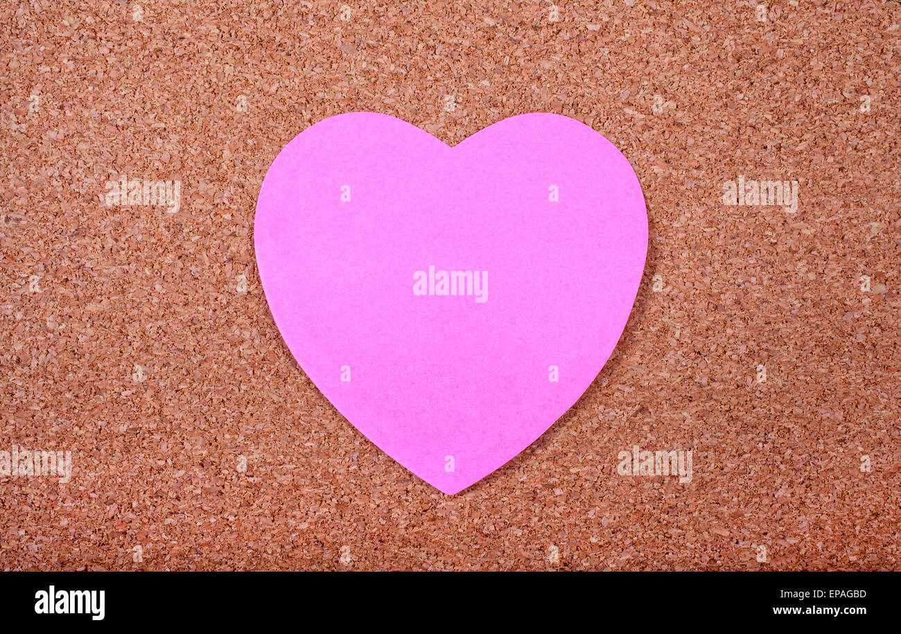 Memo paper in the shape of a Heart stuck on a noticeboard. Stock Photo