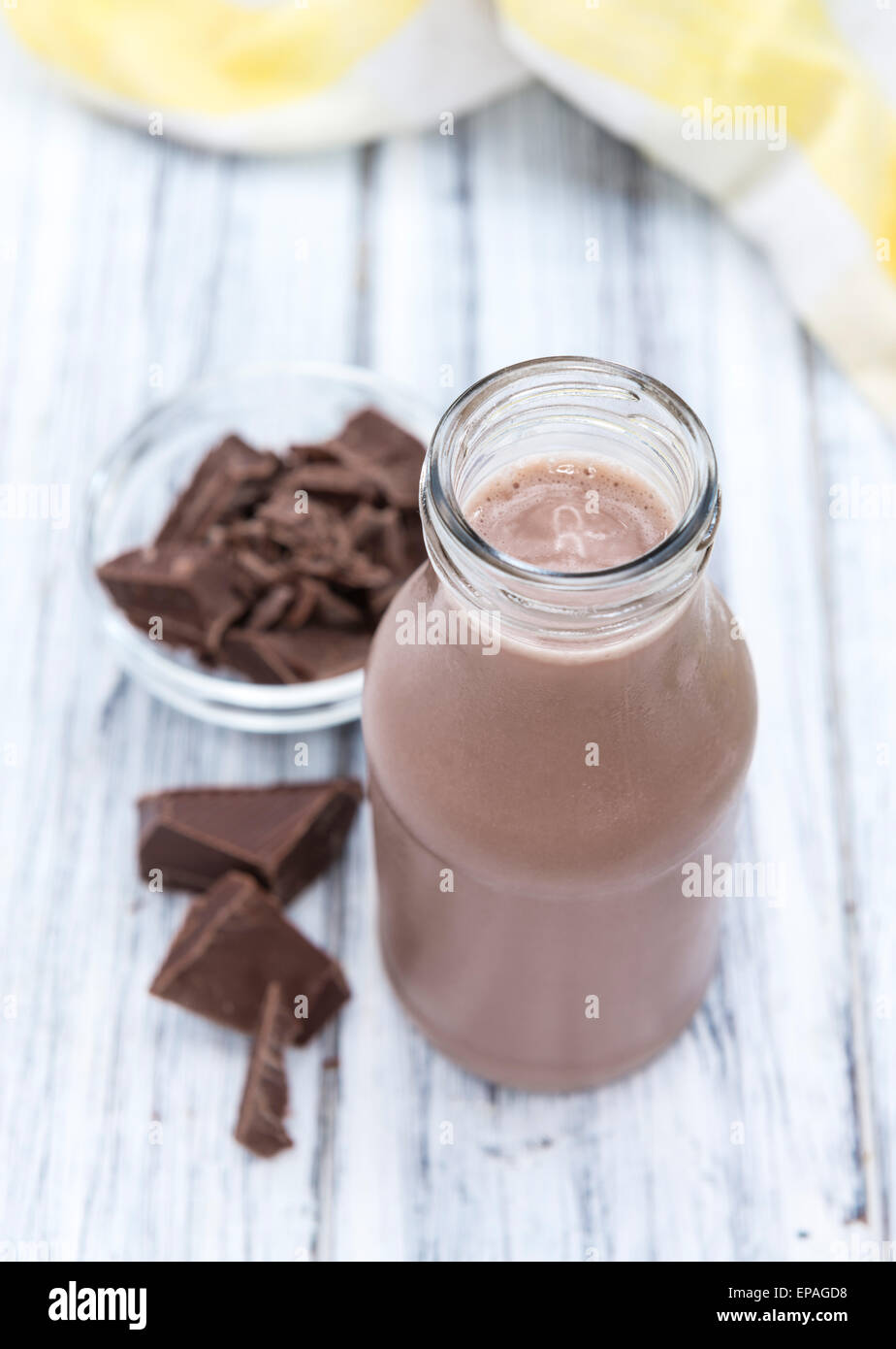 Cold Chocolate Milk drink (close-up shot) on wooden background - Stock Image