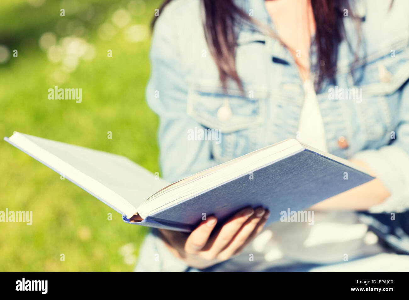 close up of young girl with book in park - Stock Image