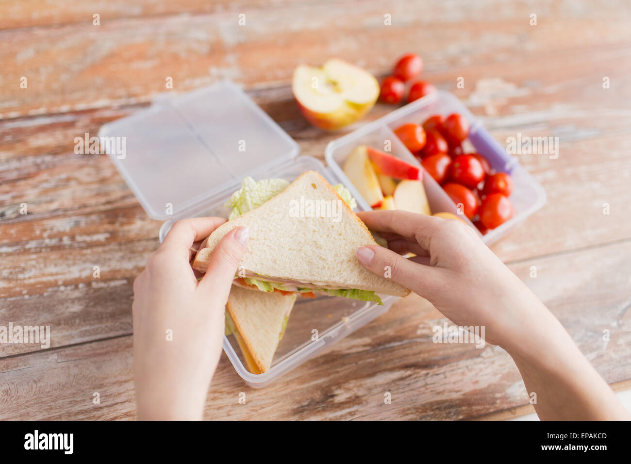 close up of woman with food in plastic container - Stock Image