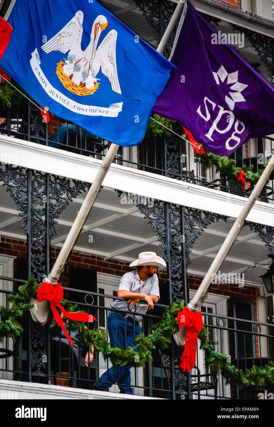 bourbon street hotels with balcony Man With Cowboy Hat And Jeans Looks Over Bourbon Street From
