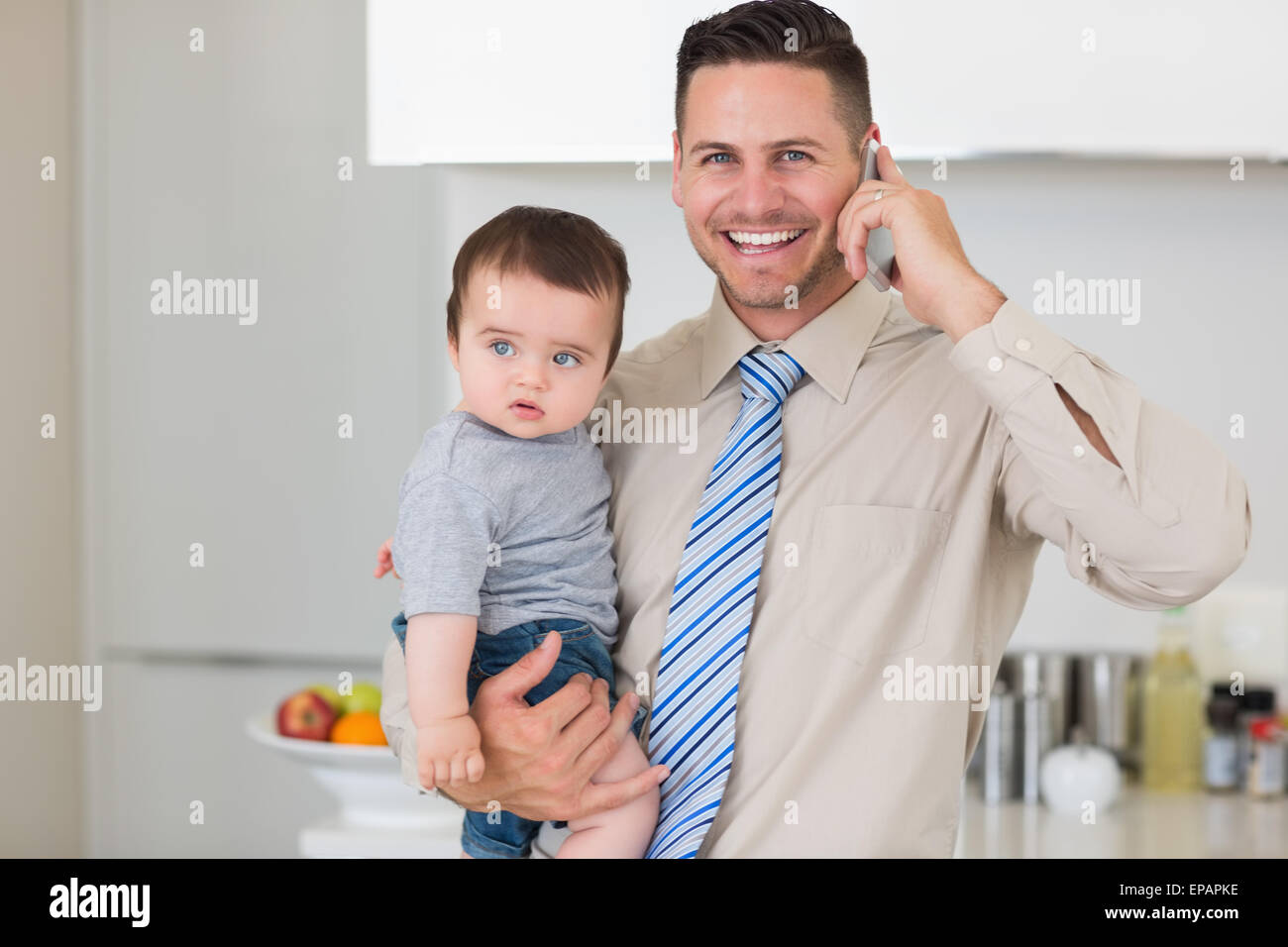 Businessman carrying baby while while using cellphone - Stock Image